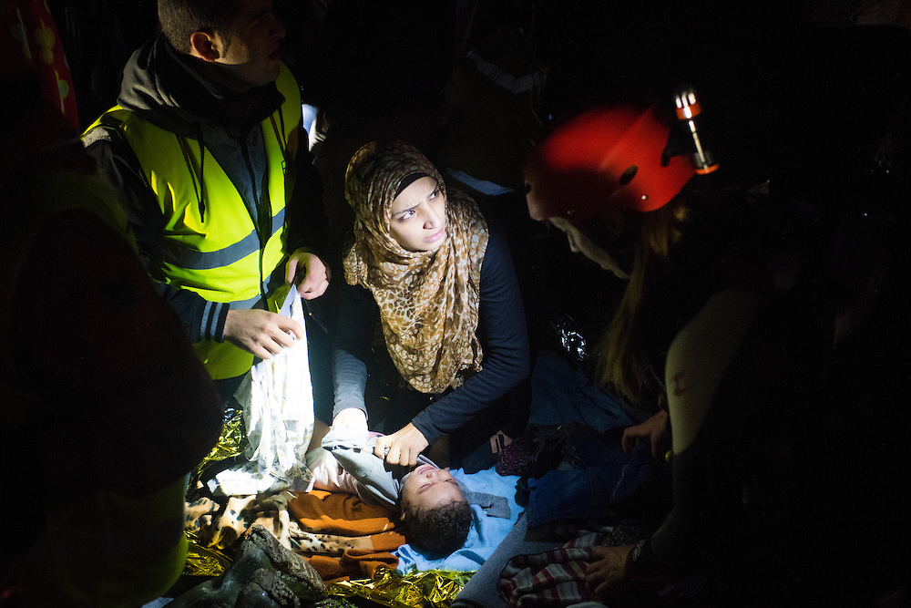 A migrant tends to her baby, with the help of aid workers, minutes after arriving on Lesbos Island in the pre-dawn hours of March 19, 2016 near Mitilini, Greece.