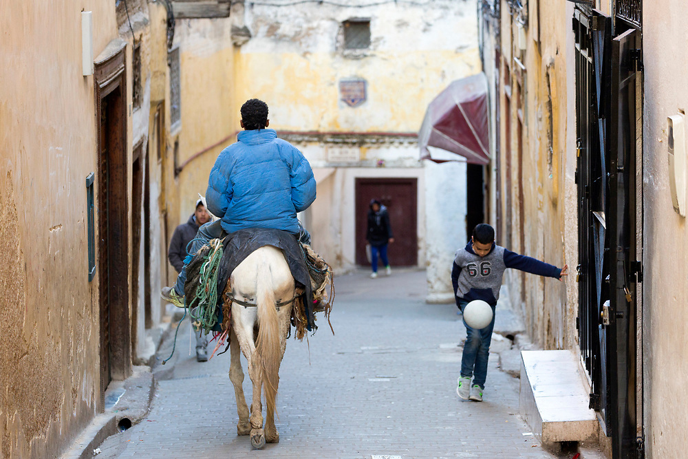 Fez, Morocco - 3rd FEBRUARY 2018 - Man riding horse through the narrow back streets and alleyways of the old Fez Medina, Middle Atlas, Morocco.
