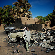 January 21, 2013 - Diabaly, Mali: A local child stands by destroyed islamic militants' armoured vehicles in central Diabaly, a day after Mali government troops regain control of the city. Diabaly was under islamist militants control since the 14th of January...Several insurgent groups have been fighting a campaign against the Malian government for independence or greater autonomy for northern Mali, an area known as Azawad. The National Movement for the Liberation of Azawad (MNLA), an organisation fighting to make Azawad an independent homeland for the Tuareg people, had taken control of the region by April 2012...The Malian government pledge to the French army to help the national troops to stop the rebellion advance towards the capital Bamako. The french troops started aerial attacks on rebel positions in the centre of the country and deployed several hundred special forces men to counter attack the advance on the ground. (Paulo Nunes dos Santos/Polaris)
