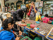08 JANUARY 2015 - BANGKOK, THAILAND:  People use a jeweler's loupe to look at amulets in a street side stall. Hundreds of vendors sell amulet and Buddhist religious paraphernalia to people in the Amulet Market, an area north of the Grand Palace near Wat Maharat in Bangkok.            PHOTO BY JACK KURTZ
