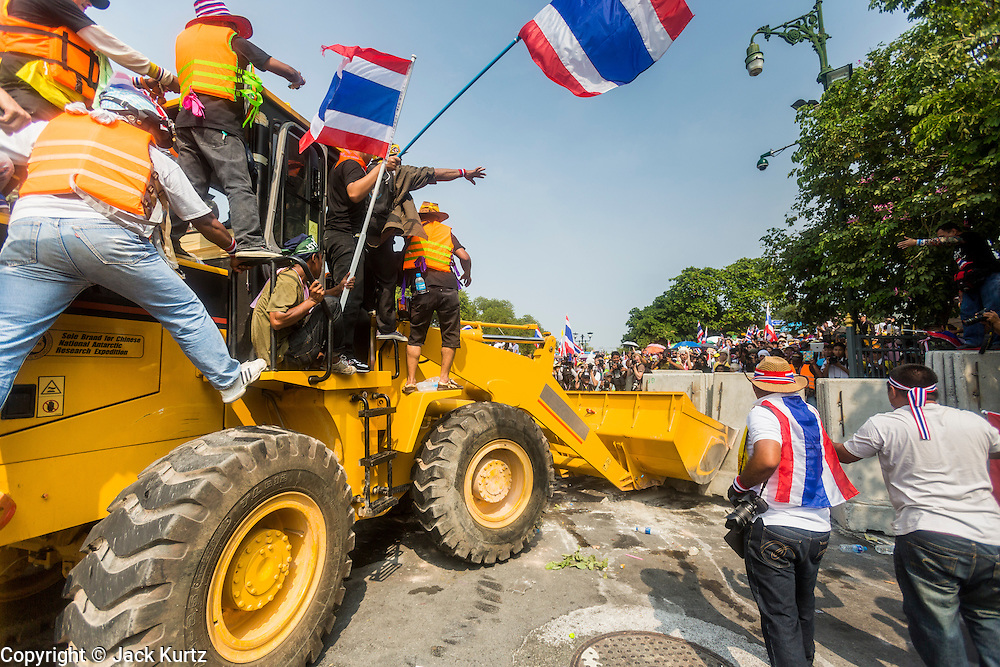 "09 DECEMBER 2013 - BANGKOK, THAILAND: Anti-government protestors use a front end loader to remove barricades blocking the roads to Government House in Bangkok. Thai Prime Minister Yingluck Shinawatra announced she would dissolve the lower house of the Parliament and call new elections in the face of ongoing anti-government protests in Bangkok. Hundreds of thousands of people flocked to Government House, the office of the Prime Minister, Monday to celebrate the collapse of the government after Yingluck made her announcement. Former Deputy Prime Minister Suthep Thaugsuban, the organizer of the protests, said the protests would continue until the ""Thaksin influence is uprooted from Thailand."" There were no reports of violence in the protests Monday.      PHOTO BY JACK KURTZ"