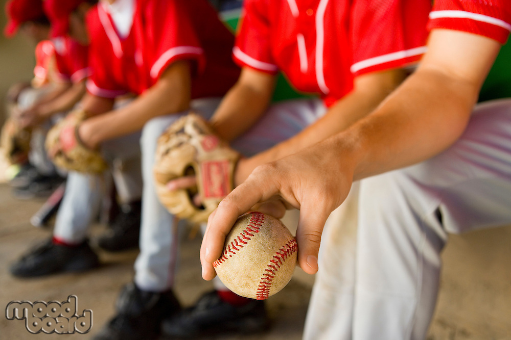 Baseball team-mates sitting in dugout (low section)