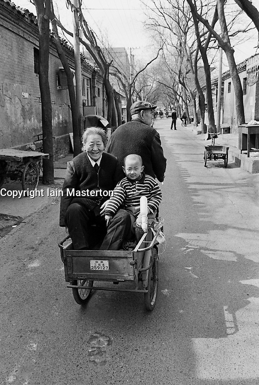 Family traveling in small tricycle cart in a traditional Beijing hutong