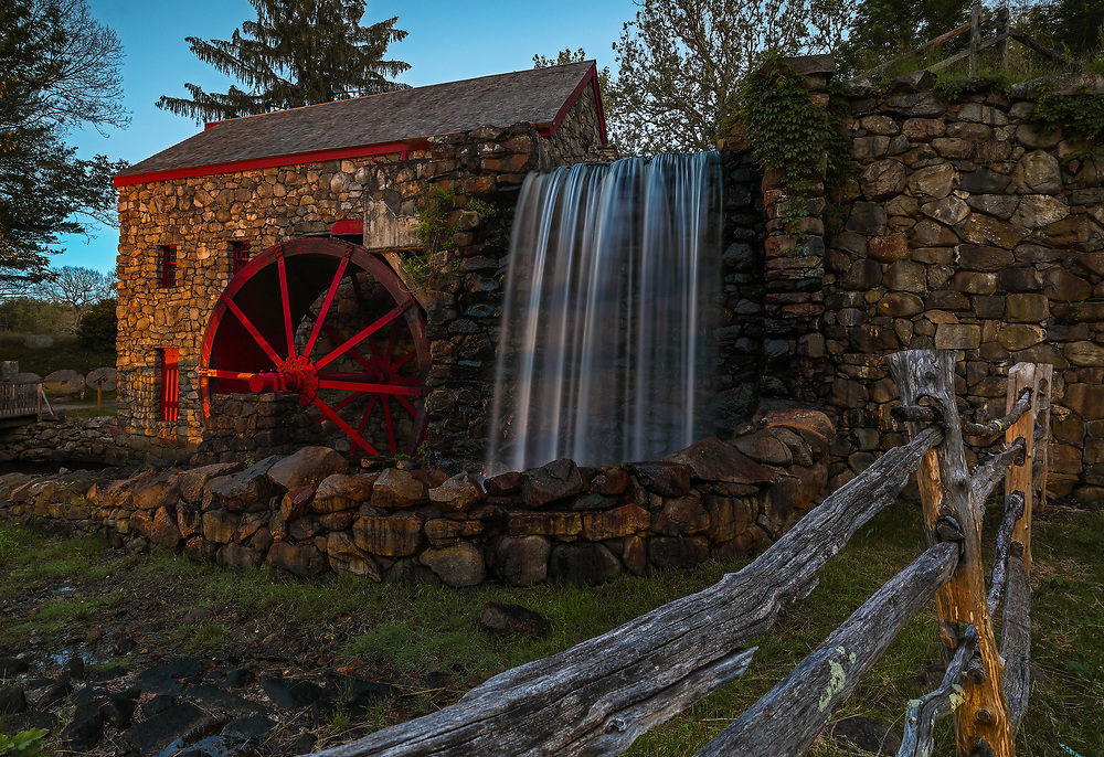 The Wayside Inn Grist Mill in Sudbury Massachusetts on a beautiful spring night in summer. A long exposure photography setting conveys the flowing water the falling waters across the Grist Mill.<br />