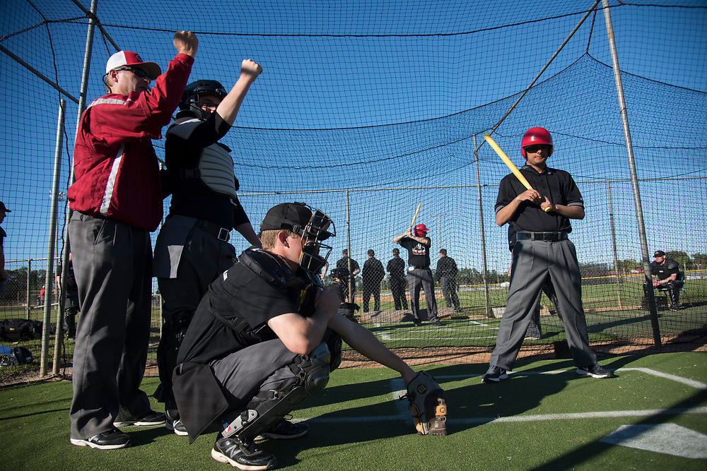 DAYTONA BEACH, FL - JANUARY 20, 2016: Students are often given one-on-one instruction in the cages, by legendary Major League Umpires like Ed Hickox, left, who stands behind a student and teaches him the proper strike mechanic. (Photo by Melissa Lyttle)