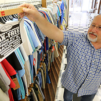 Johnny Rush, a sales clerk at Reed's on downtown Tupelo, places tax free sales signs up throughout the store to prepare for the upcoming tax free shopping weekend.