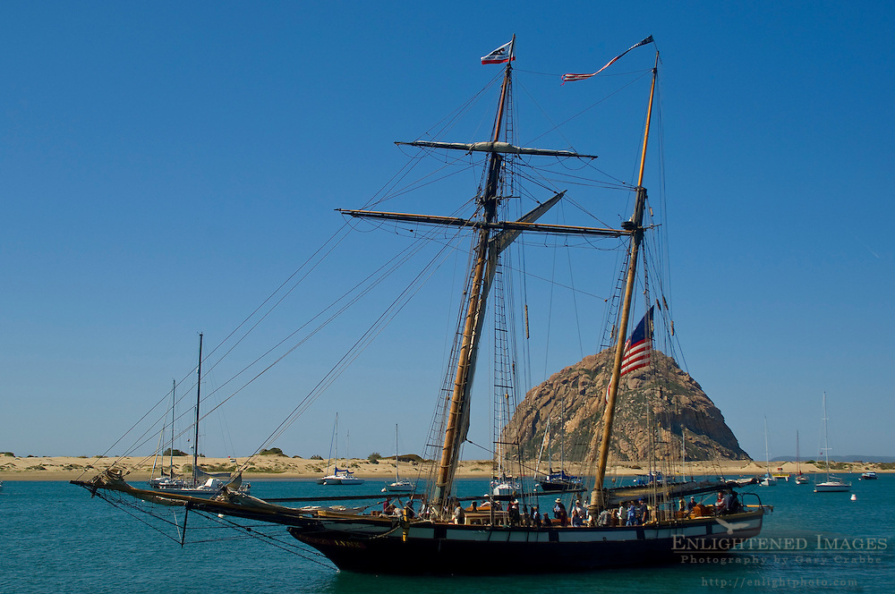 The two mast Tall Ship Schooner LYNX giving a tourist cruise in front of Morro Rock, Morro Bay, California