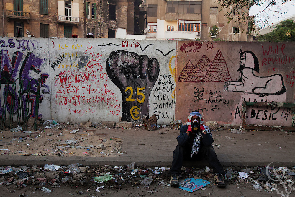An Egyptian protestor sits stunned on a sidewalk after being attacked with tear gas and buckshot barrages from nearby security forces during street battles November 21, 2011 near Tahrir square  in central Cairo, Egypt. Thousands of protestors demanding the military cede power to a civilian government authority clashed with Egyptian security forces for a third straight day in Cairo, with hundreds injured and at least 24 protestors killed.  (Photo by Scott Nelson)