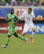 JACKSONVILLE, FL - JUNE 07:  Defender Fabian Johnson #23 of the United States heads the ball while foward Victor Moses #11 of Nigeria looks on during the international friendly match at EverBank Field on June 7, 2014 in Jacksonville, Florida.  (Photo by Mike Zarrilli/Getty Images)