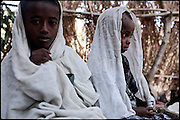 """Tesfaoun (left), 6 years old, and Buzunesh, 5 years old, are being married. In some cultures, arranged marriage is a tradition handed down through many generations. Parents who take their son or daughter's marriage into their own hands have themselves been married by the same process. Child marriages are typically made for economic or political reasons. North West of Ethiopia, on monday, Febrary 16 2009.....In a tangled mingling of tradition and culture, in the normal place of living, in a laid-back attitude. The background of Ethiopia's """"child brides"""", a country which has the distinction of having highest percentage in the practice of early marriages despite having a law that establishes 18 years as minimum age to get married. Celebrations that last days, their minds clouded by girls cups of tella and the unknown for the future. White bridal veil frame their faces expressive of small defenseless creatures, who at the age ranging from three to twelve years shall be given to young brides men adults already...To protect the identities of the recorded subjects names and specific places are fictional."""