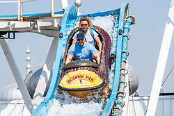 © Licensed to London News Pictures. 21/04/2019. Brighton, Members of the public cool down by taking a ride on the Brighton Palace Pier Big Splash water attraction as thousands of visitors take to the seaside resorts on the Easter Bank Holiday Sunday. Photo credit: Hugo Michiels/LNP