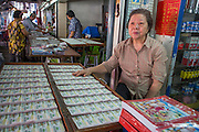 03 JANUARY 2013 - BANGKOK, THAILAND:  A lottery ticket seller in her booth along Sukhumvit Soi 77 in Bangkok. About 20 million Thais, nearly ⅓ of the country's 65 million people, play lottery type games. The lotteries were brought to Thailand two hundred years ago by Chinese immigrants. Lottery agents are usually friends who collect bets but do not ask for money before the drawing.   PHOTO BY JACK KURTZ