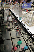 street scene with people walking reflected in mirrored roof Madrid Gran Via
