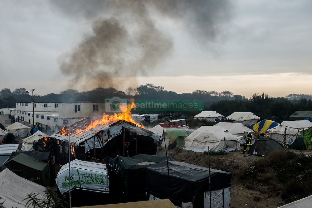 October 26, 2016 - Calais, France - A firefighter extinguish in the Calais Jungle a burning hut. Huge fires destroyed a mayor part of the refugee camp today. (Credit Image: © Markus Heine/NurPhoto via ZUMA Press)