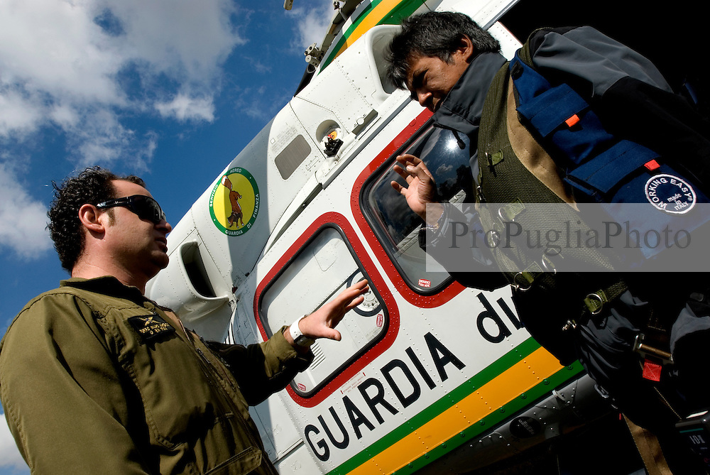 Puglia, Italy. The Pilot of the Italian Coast Guard gives a brief to a TV cameramen before bording into th Helicopter