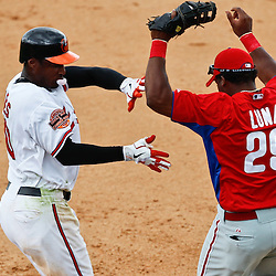 March 20, 2012; Sarasota, FL, USA; Philadelphia Phillies first baseman Hector Luna (29) avoids a collision with Baltimore Orioles center fielder Adam Jones (10) on ground out during the bottom of the seventh inning of a spring training game at Ed Smith Stadium.  Mandatory Credit: Derick E. Hingle-US PRESSWIRE