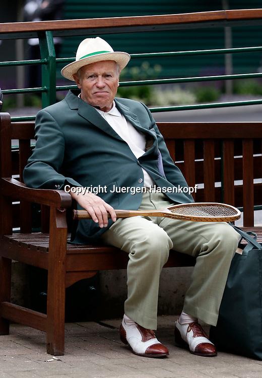 Wimbledon Championships 2011,AELTC,London,.ITF Grand Slam Tennis Tournament . altmodisch gekleideter aelterer herr sitzt auf einer Holzbank mit und haelt einen antiken Tennisschlaeger aus Holz,.Renshaw Schlaeger,Fan,Ganzkoerper,Hochformat,Feature,