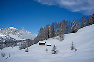 Wooden barns on a snowy slope at the Alta Badia ski resort ski resort near Corvara in The Dolomite Mountains, South Tyrol, Italy