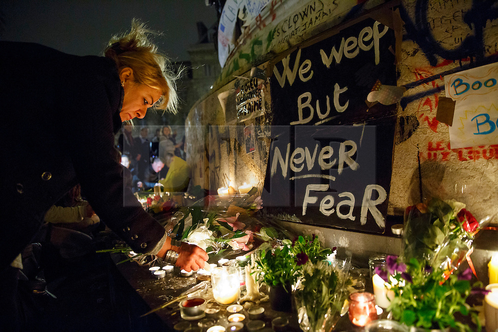 © Licensed to London News Pictures. 14/11/2015. Paris, France. Mourners leaving candles and flowers at Place de la République in Paris, France following the Paris terror attacks on Saturday, 14 November 2015. Photo credit: Tolga Akmen/LNP