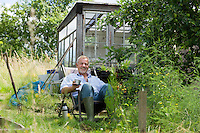 Senior man pouring drink sitting in garden