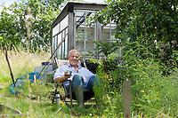 Senior man pouring drink sitting in garden