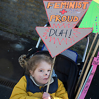 London UK. January 21st 2017. A toddler in a buggy holds a placard saying 'Feminist and Proud'. An estimated 100,000 protesters took part in a Women's March from the US Embassy in Grosvenor Square to Trafalgar Square as part of an international campaign on the first full day of Donald Trump's Presidency of the United States.