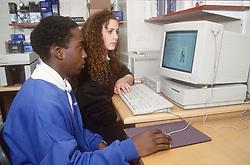 Secondary school pupils sitting at desk using computer,