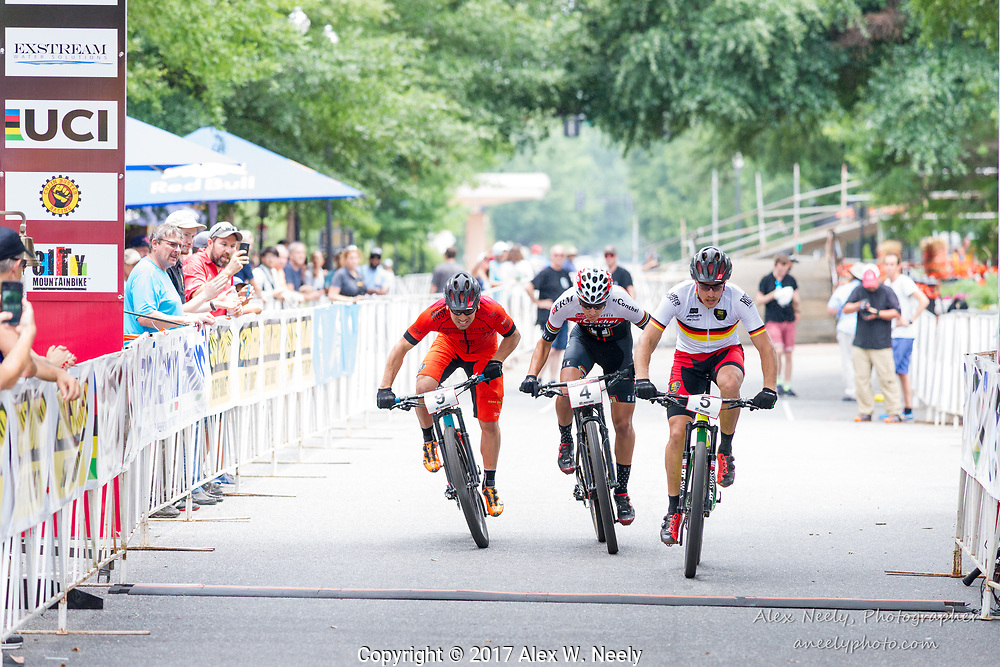 Simon Gegenheimer (5-GER), Alberto Mingorance Fernández (4-ESP) and Steffen Thum (9-GER) battle for position during the first of two laps of the second heat of the quarter finals at the 2017 UCI Mountain Bike Eliminator World Cup race in Columbus, GA (USA) on June 4, 2017.