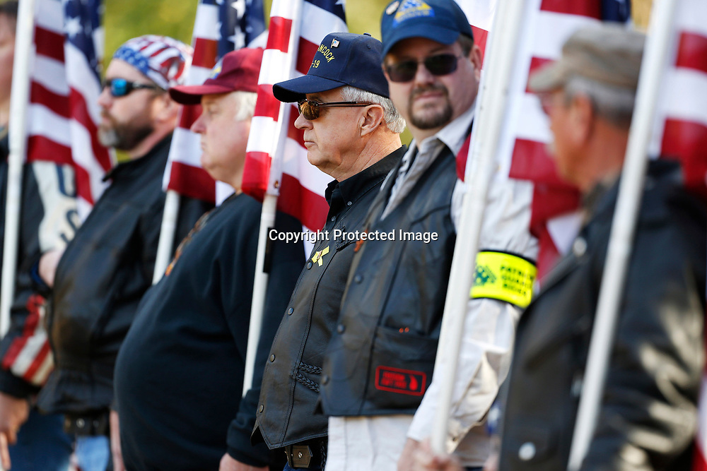 """Members of the Patriot Guard stand with American flags during the funeral for Sgt. Kevin """"Gale"""" Stauffer who was shot and killed Monday after responding to a bank robbery Friday afternoon at the Tupelo Memorial Gardens."""