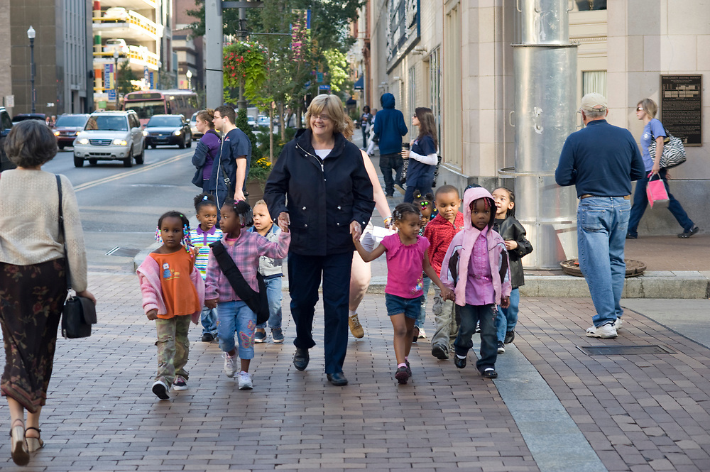 Director Lynne Geidel crosses 6th Street with her preschool students from Small World 2 Early Learning & Development Center while taking a walk in downtown Pittsburgh.