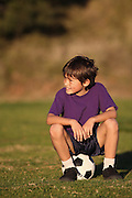 Boy sits on soccer ball looking to side in late afternoon sun - with copy space above and to left