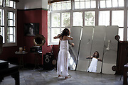 YANGON, MYANMAR, MARCH 2012: Ha Moon tries a new outfit in the rehearsal room at Nicole May's house in central Yangon.<br /> Burma is a country in Transition. And if that hasn't been made clear enough by the political debates and the recent by-elections, meet the Me N Ma Girls, the first girlband in the country.<br /> The timing couldn't be better. After the April 1st elections in 2012 an always increasing number of investors from all over the world has been visiting Myanmar. After decades of military regime and isolation, the strings of censorship have started loosening up. The government censors in fact for years have banned songs and articles, deleting anything that was seen as &quot;to provocative&quot; such as leather outfits and colored wigs.<br /> Describing themselves as Myanmar's first all-girl group, under the management of the Australian dancer and choreographer Nicole May, these five women - coming from either Buddhist or Catholic background and formerly known as Tiger Girls - not only have been challenging censorship laws but they're as well trying to win hearts in a society that in many ways remains man-dominated and socially conservative.<br /> In a country that has been locked up for years, the Me N Ma Girls, embracing western pop culture with skimpy outfits and catchy songs, show with every performance the will of the Burmese youth to come out of a decades-long isolation.<br /> Five girls leading a new form of rebellion: the kind that questions roles and cultural norms.