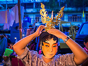 16 JANUARY 2015 - BANGKOK, THAILAND: A performer with the Sai Yong Hong Teochew Opera Troupe puts on her costume before performing at the Chaomae Thapthim Shrine, a Chinese shrine in a working class neighborhood of Bangkok near the Chulalongkorn University campus. The troupe's nine night performance at the shrine is an annual tradition and is the start of the Lunar New Year celebrations in the neighborhood. Lunar New Year, also called Chinese New Year, is officially February 19 this year. Teochew opera is a form of Chinese opera that is popular in Thailand and Malaysia.    PHOTO BY JACK KURTZ