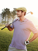 Young male golfer standing on course holding club on shoulder