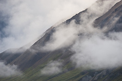 Clouds swirl around the sides of Gravel Mountain as seen from the Eielson Visitor Center in Denali National Park and Preserve in Alaska.