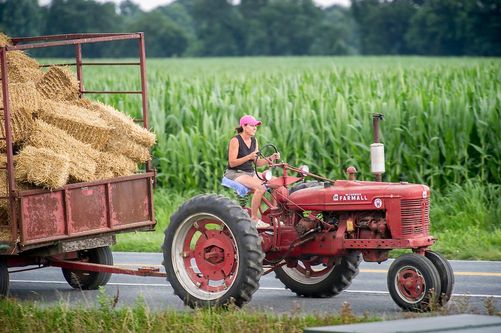 Woman farmer hauling hay wagon with tractor