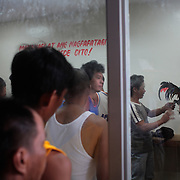 THE PHILIPPINES (Boracay). 2009. Roosters are prepared for the fight as a three inch razor sharp blade is attached to their left ankles as spectators watch at the cockfighting held at the Boracay Cockpit, Boracay Island. Photo Tim Clayton <br /> <br /> Cockfighting, or Sabong as it is know in the Philippines is big business, a multi billion dollar industry, overshadowing Basketball as the number one sport in the country. It is estimated over 5 million Roosters will fight in the smalltime pits and full-blown arenas in a calendar year. TV stations are devoted to the sport where fights can be seen every night of the week while The Philippine economy benefits by more than $1 billion a year from breeding farms employment, selling feed and drugs and of course betting on the fights...As one of the worlds oldest spectator sports dating back 6000 years in Persia (now Iran) and first mentioned in fourth century Greek Texts. It is still practiced in many countries today, particularly in south and Central America and parts of Asia. Cockfighting is now illegal in the USA after Louisiana becoming the final state to outlaw cockfighting in August this year. This has led to an influx of American breeders into the Philippines with these breeders supplying most of the best fighting cocks, with prices for quality blood lines selling from PHP 8000 pesos (US $160) to as high as PHP 120,000 Pesos (US $2400)..