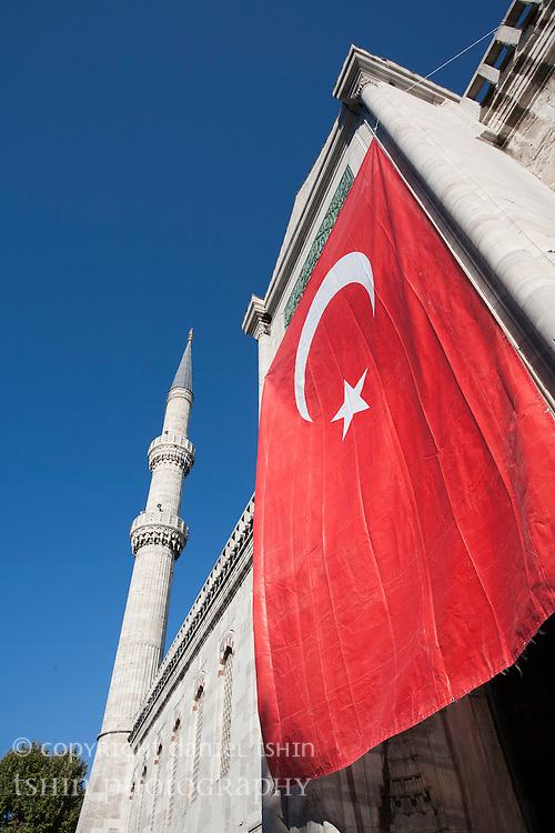 A large Turkish flag flying above a gateway, around Victory Day in late August.