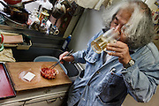 Kawasaki, November 6 2014 - Japanese artist Tatsumi ORIMOTO, 69, at home drinking sake while taking care of his 97-year-old mother.