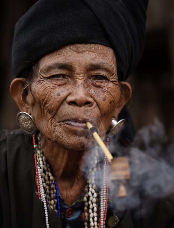 KYAING TONG, MYANMAR - CIRCA DECEMBER 2017: Portrait of elder woman of the Wan Sai Akha Village in Kyaing Tong smoking.