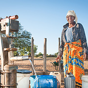 CAPTION: Davidzo collects water from a borehole pump, early in the morning. These pumps can be very hard for women, children and the elderly to use, and they often have to travel long distances to reach these sources of water before carrying the heavy buckets back on their heads. LOCATION: Mawoneke Village, Chivi District, Masvingo Province, Zimbabwe. INDIVIDUAL(S) PHOTOGRAPHED: Davidzo Govore.