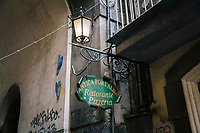 """NAPLES, ITALY - 20 NOVEMBER 2018: The sign  of the Antica Pizzeria Port'Alba, where the pizza a portafoglio (wallet pizzas), is seen here in Naples, Italy, on November 20th 2018.<br /> <br /> My Brilliant Friend (Italian: L'amica geniale) is an Italian-American drama television miniseries based on the novel of the same name by Elena Ferrante. The series follows the lives of two perceptive and intelligent girls, Elena (sometimes called """"Lenù"""") Greco and Raffaella (""""Lila"""") Cerullo, from childhood to adulthood and old age, as they try to create lives for themselves amidst the violent and stultifying culture of their home – a poor neighborhood on the outskirts of Naples, Italy. My Brilliant Friend is a co-production between American premium cable network HBO and Italian networks RAI and TIMvision"""