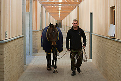 © Licensed to London News Pictures. 07/02/2012. LONDON, UK. A member of the King's Troop Royal Horse Artillery leads a horse through new purpose built and carbon neutral barracks in Woolwich. Previously based at St John's Wood since 1947, the Royal Artillery's ceremonial unit today arrived at their new home at Napier Barracks in Woolwich Photo credit: Matt Cetti-Roberts/LNP