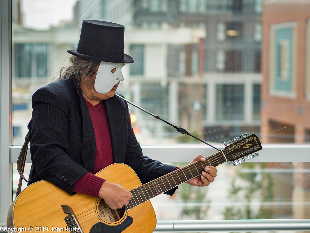 """30 OCTOBER 2019 - DES MOINES, IOWA: RANDY KONG performs in the Des Moines Skywalk system. Kong said he's been busking for about nine years. He said he started when his band broke up and busking might be way to """"get a hot dog and a coke, and now it's turned into a career."""" He usually performs during the lunch hour and is a regular sight in the skywalk system. In October he hands out candy and sings Halloween themed songs while wearing a """"Phantom of the Opera"""" like mask. In December he does a Christmas themed show and in February he does a Valentines themed show.        PHOTO BY JACK KURTZ"""