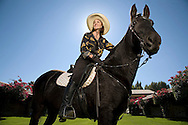 pretty middle aged Woman with brimmed hat riding her black horse back lit by the sun. Stable in background.