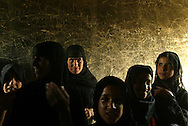 Muslim women take refuge from the sun in their adobe house set between beds of water and reed in the outskirts of the town of Nasariyah Thursday June 05, 2003.