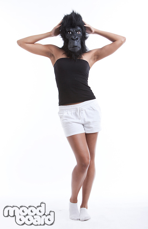 Portrait of young woman wearing gorilla mask against white background