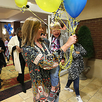 Krissy McKinney, of Nettleton, laughs with her son Bo, 3, as they walk out for the balloon release at the Le Bonheur Family Affair event Monday night at the BancorpSouth Conference Center in Tupelo. For eight weeks the Mckinney family, along with two other families, the Francis and Robertson families, have been raising money in a friendly competition to benefit Le Bonheur Children's Medical Center. Items were on display for a silent auction would count to the families fundraiaing totals.