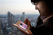 Yuuya Iwama playing the Love Plus dating game on his Nintendo DS on the top of one of the Tokyo Metropolitan Government buildings, a popular sightseeing location offering a good view of Tokyo.