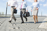 Businesspeople running on bridge